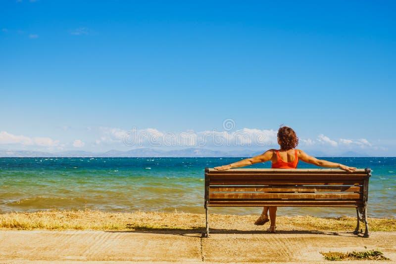 长凳的旅游妇女享受海视图的 库存图片