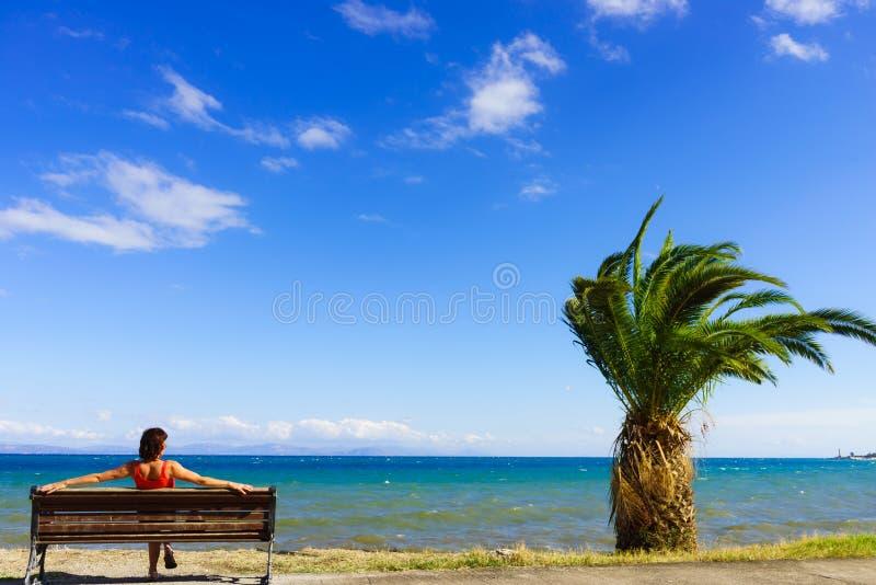 长凳的旅游妇女享受海视图的 免版税库存图片