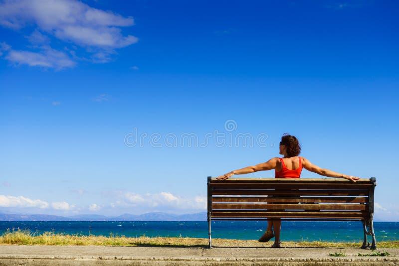 长凳的旅游妇女享受海视图的 库存照片