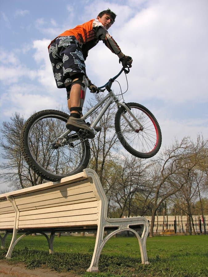 长凳骑自行车的人 免版税库存图片