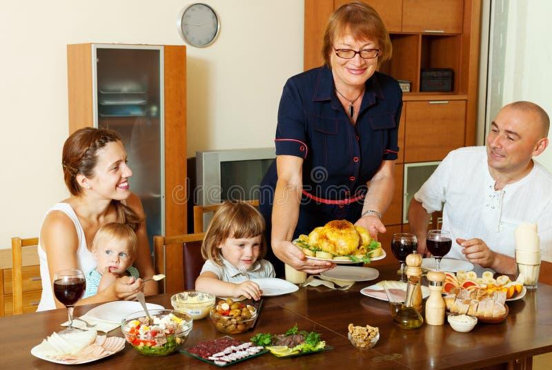 年长制表的妇女服务被烘烤的鸡 免版税库存图片