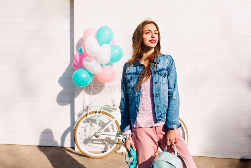 长发疲乏的女孩在自行车游览以后敬佩风景,拿着背包和耳机 迷人的年轻女人  图库摄影