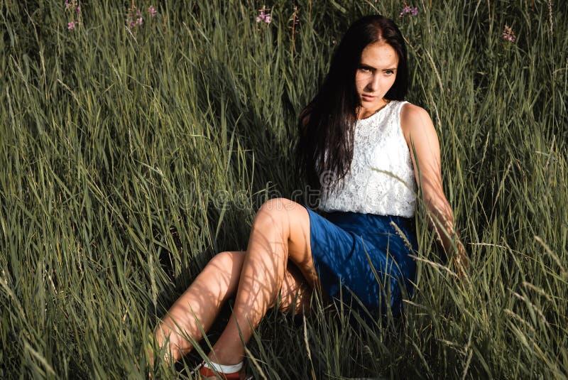 长发青少年的女孩坐草草甸 免版税库存图片