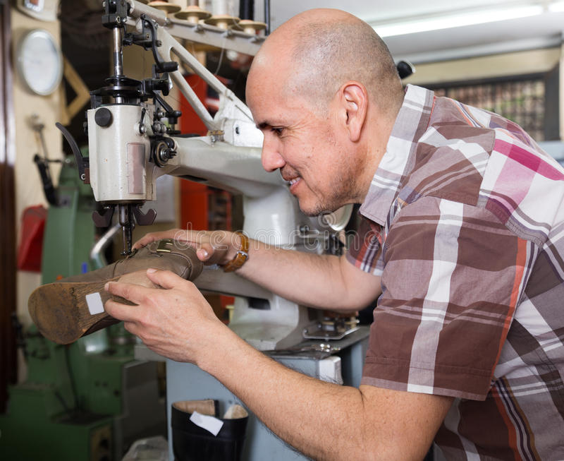 年长在针车床的工作员缝合的皮靴在车间 免版税库存照片