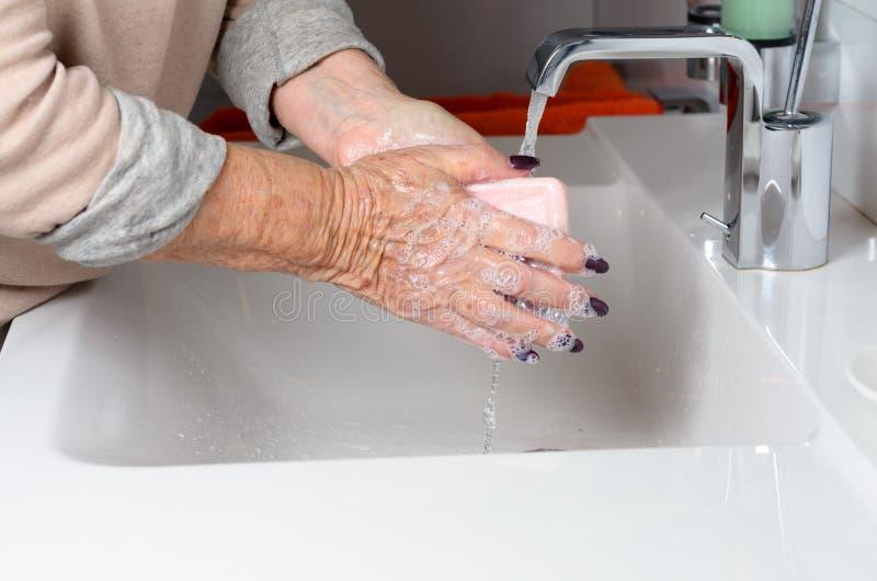 年长在轻拍下的妇女洗涤的手 免版税库存照片