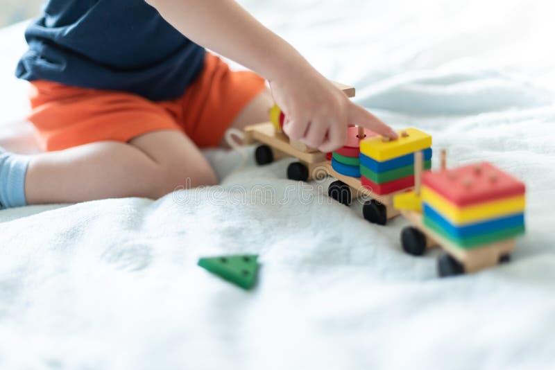 长大和孩子休闲概念 使用与一列色的木火车的孩子 孩子修造建设者 免版税库存照片