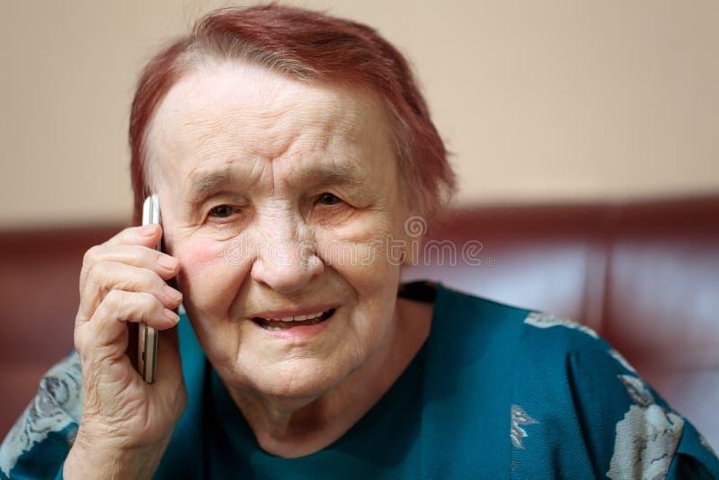 年长夫人谈话在一个手机 免版税库存照片