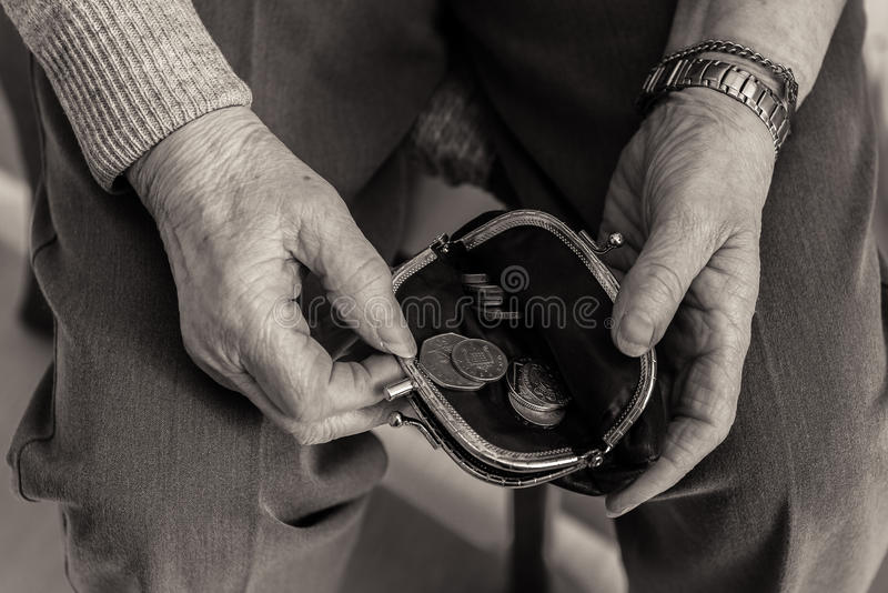 年长夫人` s递检查在她的钱包的金钱 免版税图库摄影