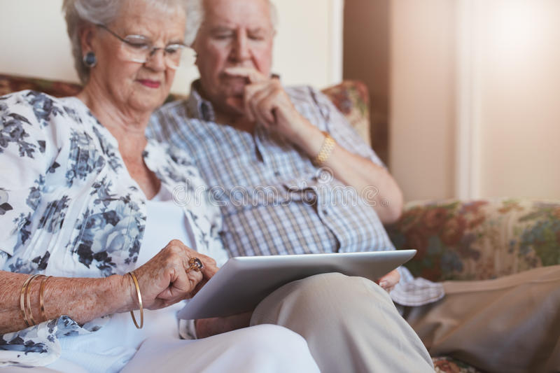 年长夫妇在家使用数字式片剂 库存照片