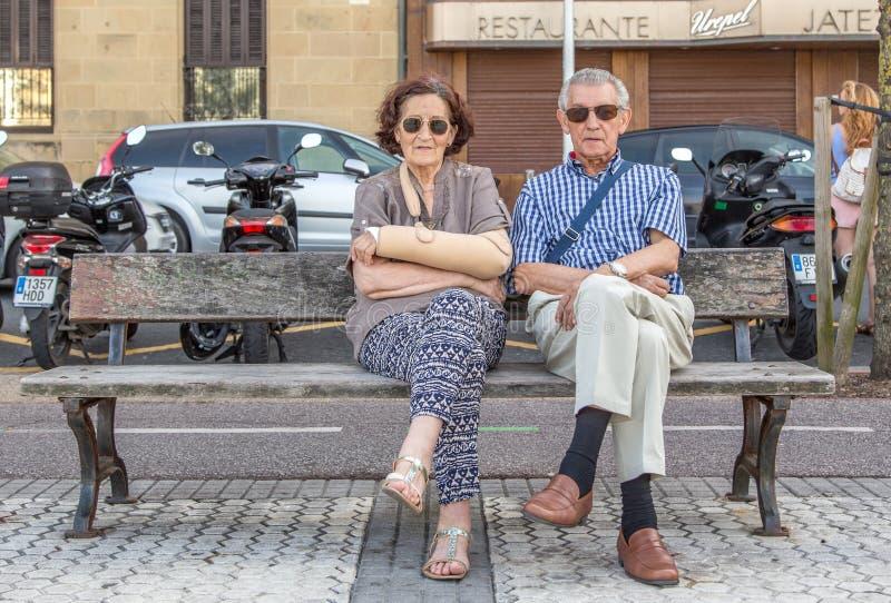 年长夫妇坐一条长凳在西班牙 免版税图库摄影