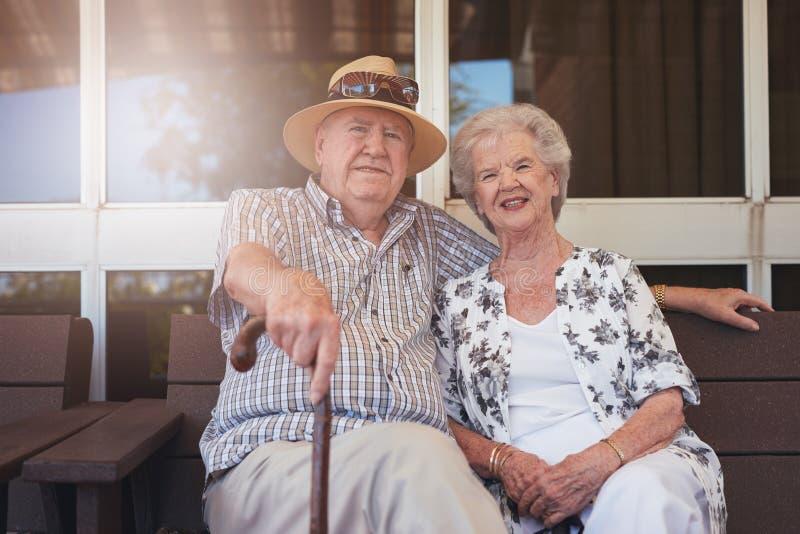 年长夫妇坐在长凳放松了户外 库存图片