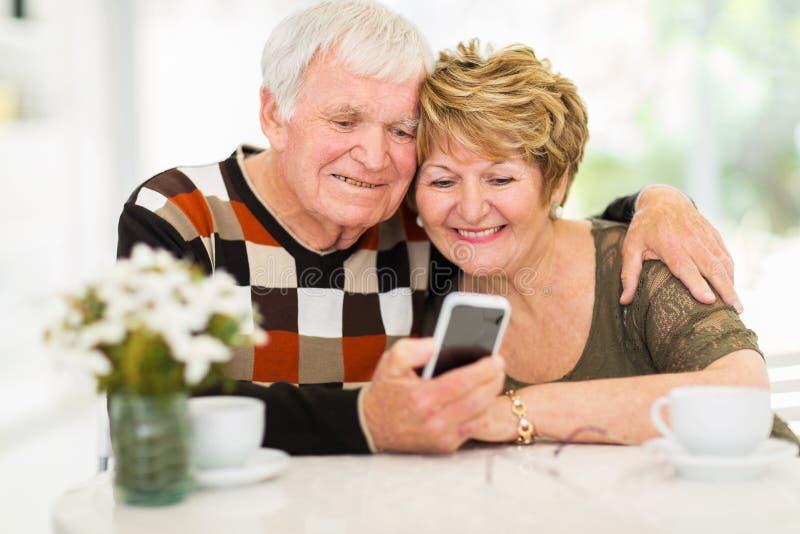 年长夫妇巧妙的电话 免版税库存图片