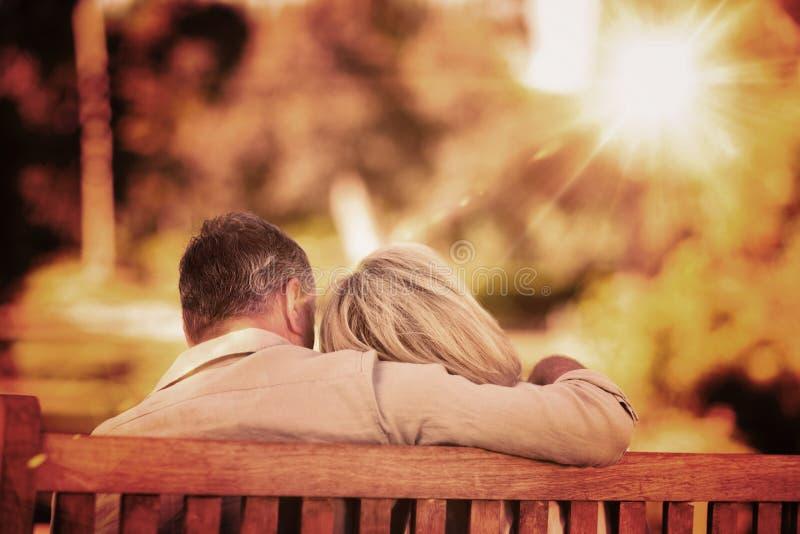 年长夫妇的综合图象坐与他们的长凳回到照相机 免版税图库摄影