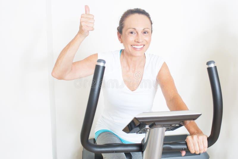 年长妇女喜欢循环在健身房 免版税库存照片