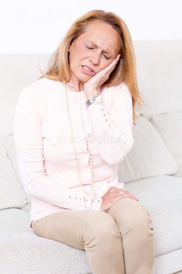 年长妇女在与牙痛的床上 免版税库存照片