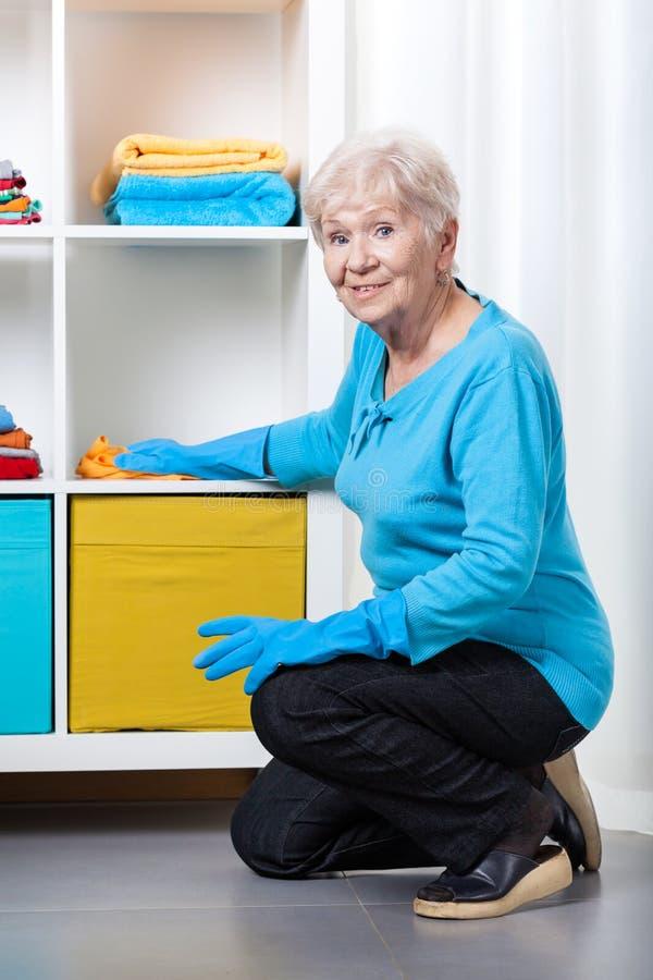 年长妇女打扫灰尘架子 免版税库存照片