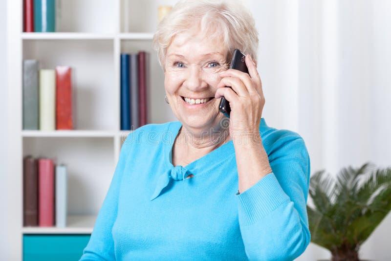 年长妇女谈话在电话 免版税库存照片