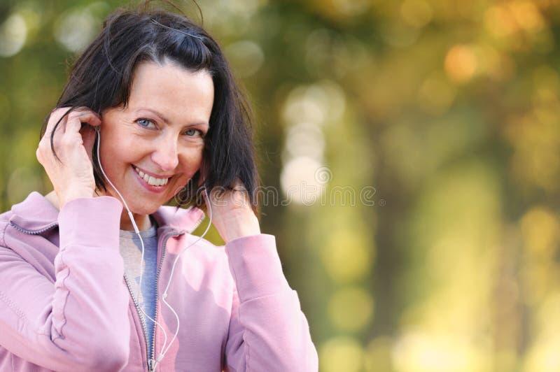年长妇女画象在公园准备跑步与耳机 免版税图库摄影
