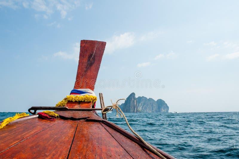 长尾巴小船的前面在公海的有岩石的 在清楚的绿色水的传统长尾巴小船在对玛雅人海湾海滩的途中 免版税图库摄影
