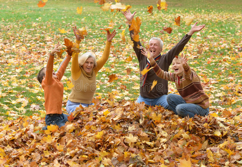 年长投掷叶子的夫妇和孩子 免版税库存照片