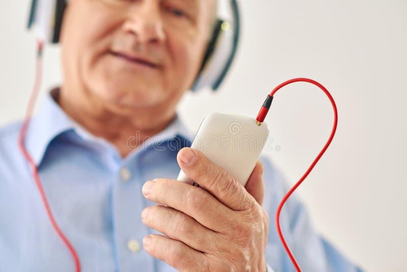 年长拿着电话的人听的音乐 免版税图库摄影