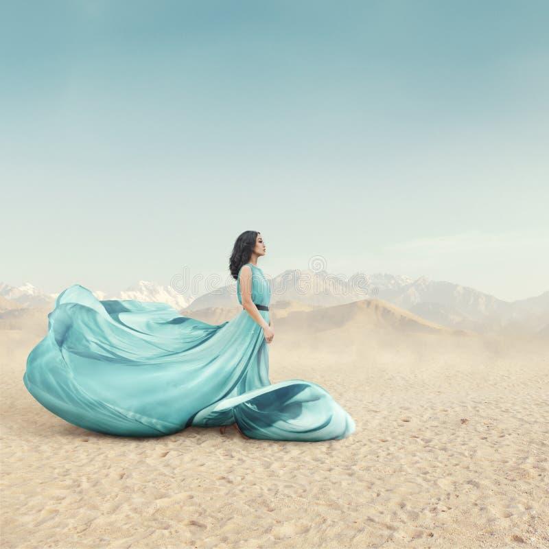 长振翼的礼服摆在的美丽的年轻女人室外 免版税库存照片