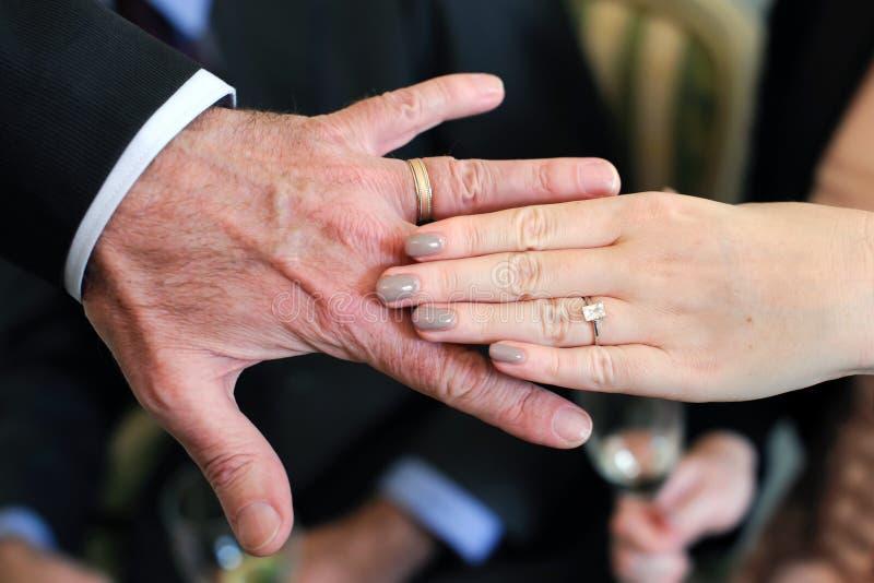 年长新娘和新郎的手 免版税库存图片