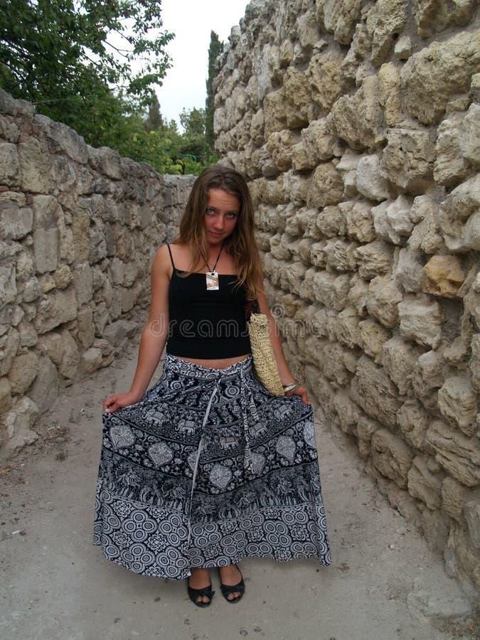 长期女孩在裙子smilinig石墙附近 免版税图库摄影