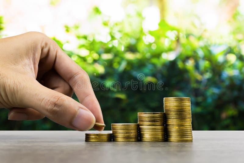 长期投资或赚钱与正确的概念 投入在堆的商人手在一张木桌上的硬币与 免版税图库摄影