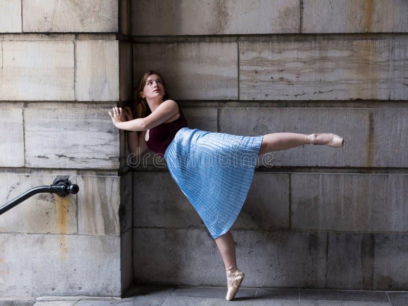 长期被打褶的裙子和pointe的芭蕾舞女演员穿上鞋子在充分地延长的脚的身分 免版税库存图片