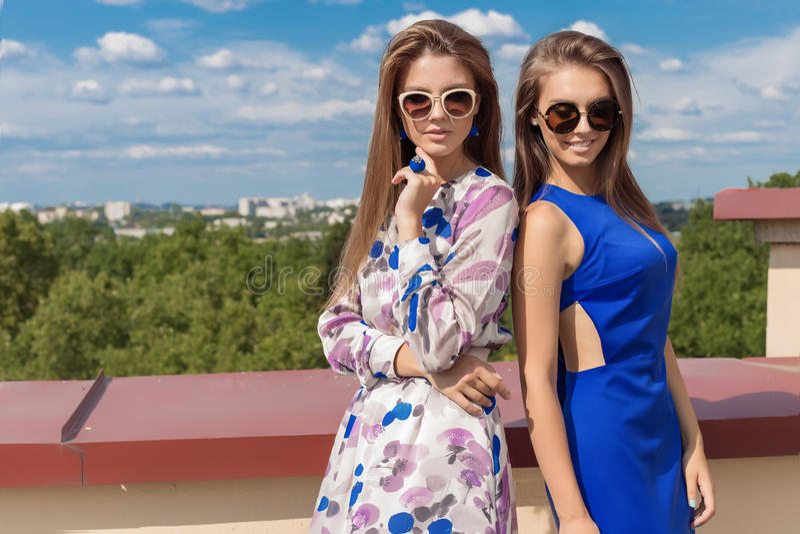 长期krasiivyh时兴的礼服的两个美丽的性感的少妇朋友在基于大阳台的太阳镜在明亮下 库存图片