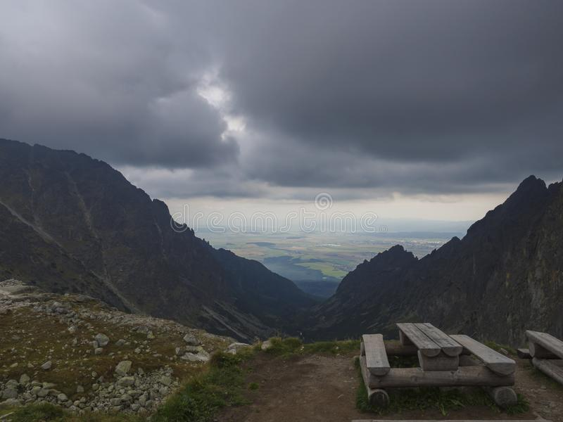 长木凳和桌吃的在高Tatra山在斯洛伐克有看法在谷和有雾的天空 库存照片