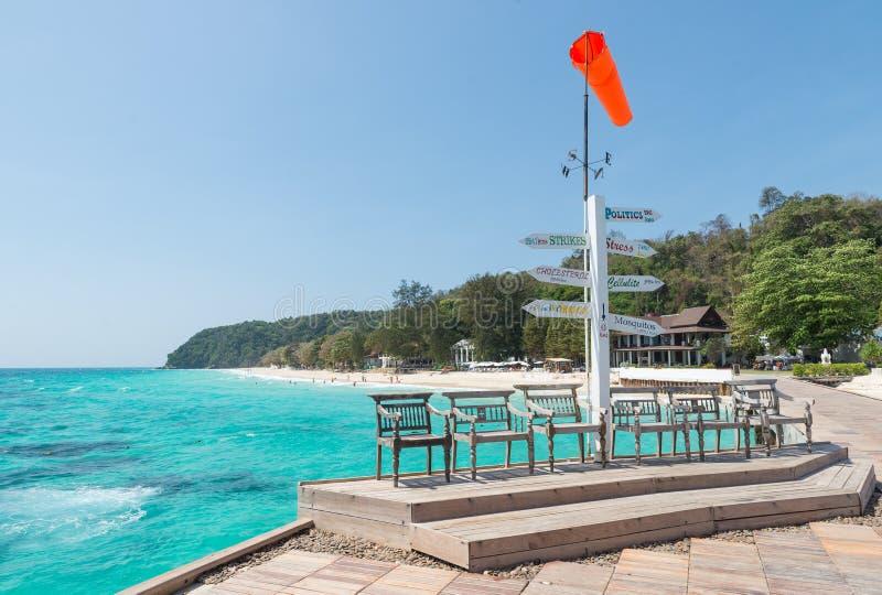 长木凳和橙色风向仪在海边 免版税库存图片