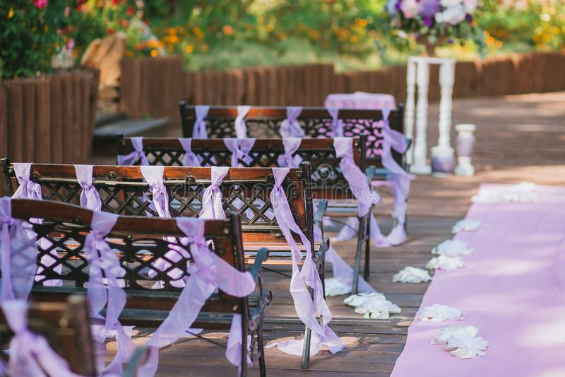 长木凳在婚礼区域在庭院里,装饰用紫色丝带 库存照片