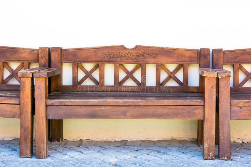 长木凳在房子后站立在墙壁附近 免版税库存照片