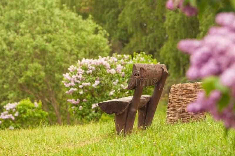 长木凳在有树的一个野花绿色庭院里 免版税图库摄影