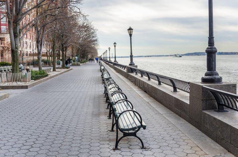 长木凳行在河沿小径的 库存图片