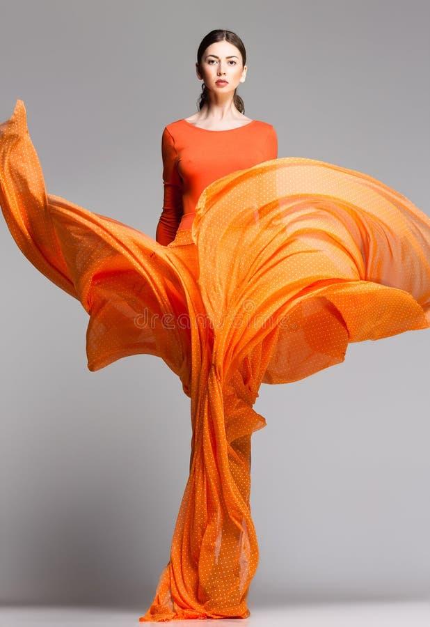 长橙色礼服摆在的美丽的妇女严重 库存照片