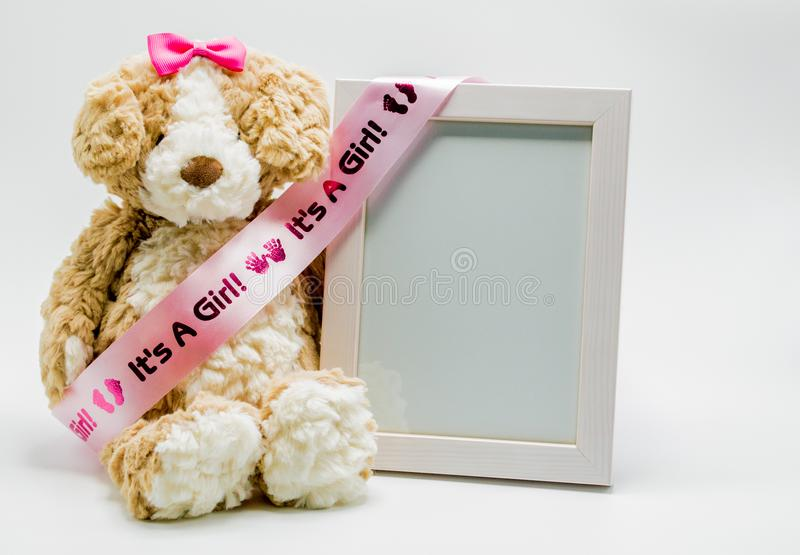 长毛绒玩具熊和空的画框与`它` s女孩`丝带 库存照片