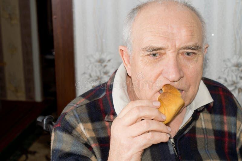 年长沉思食人小圆面包 库存照片