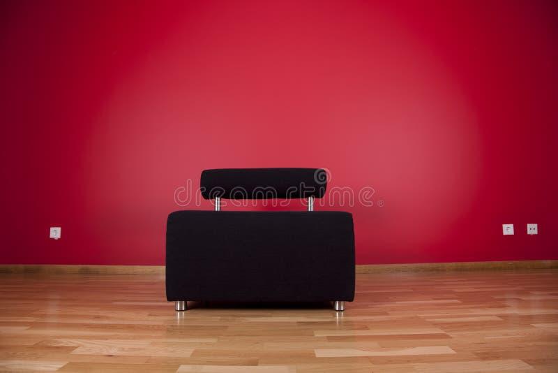 长沙发下红色墙壁 免版税库存图片