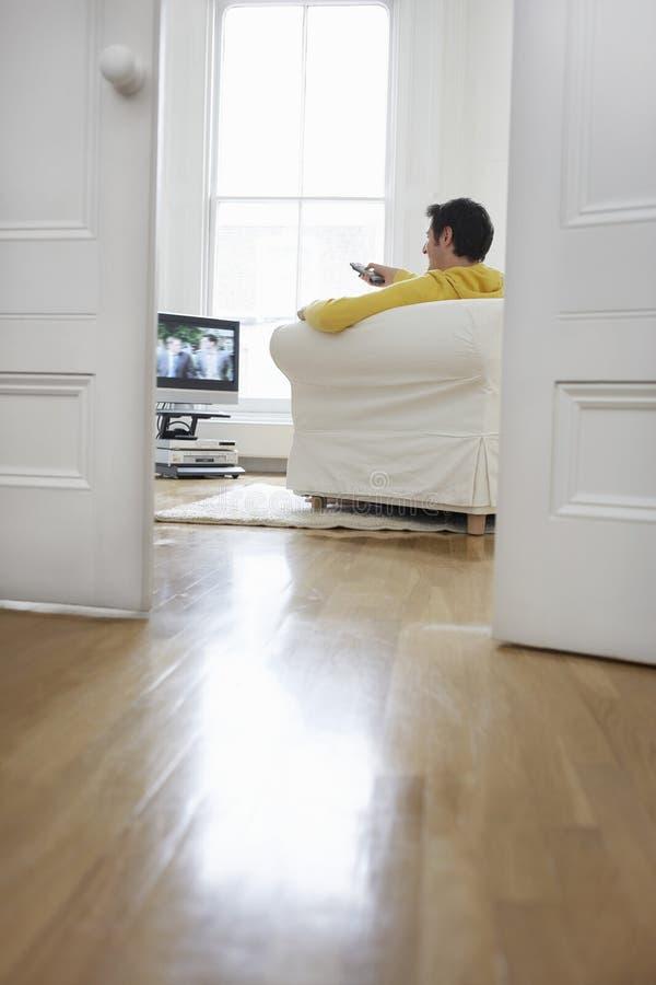 长沙发和观看的电视的人 免版税库存照片
