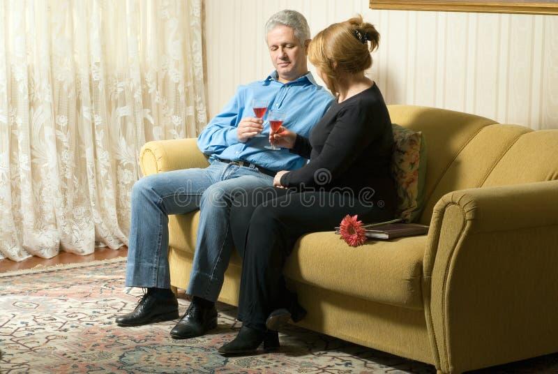 长沙发夫妇喝水平 库存照片