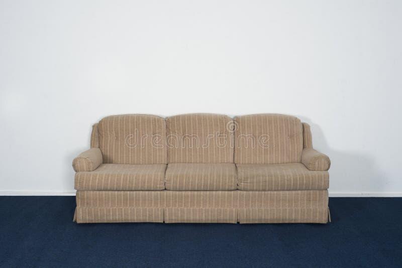 长沙发或达文波特,蓝色地毯,空白的白色墙壁 免版税库存图片