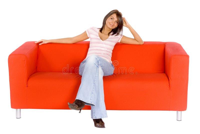 长沙发橙色微笑的妇女 免版税库存图片