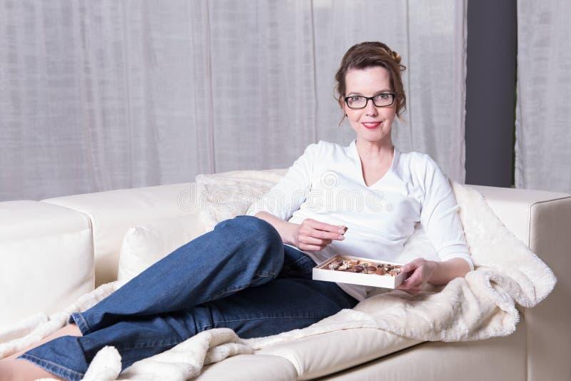 长沙发的可爱的妇女吃巧克力的 免版税库存照片