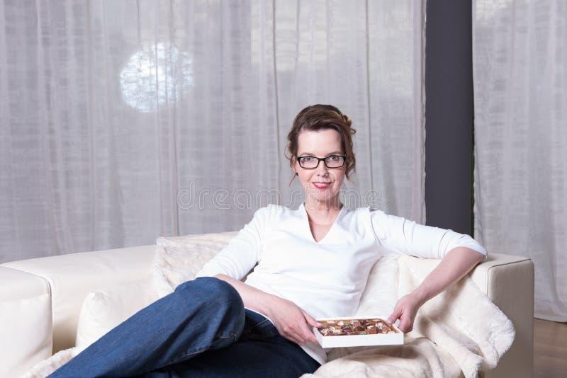 长沙发的可爱的妇女吃巧克力的 库存图片