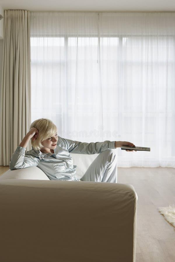 长沙发的妇女看电视的 库存图片