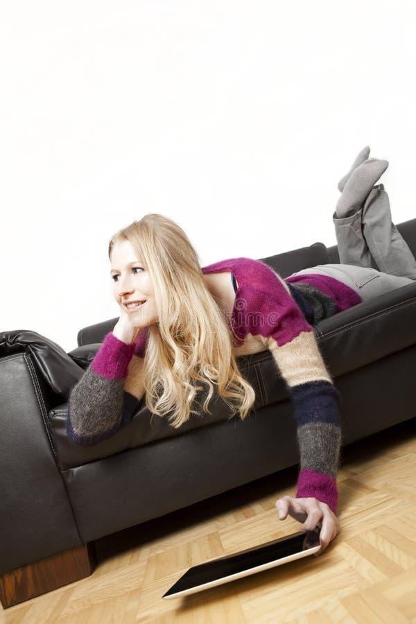 长沙发的幸运妇女使用她的片剂个人计算机 库存照片