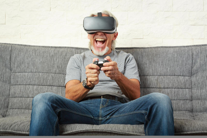 长沙发的老人,打Vr比赛 免版税图库摄影